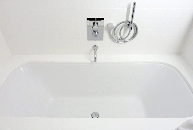 a view of a bath with. a side mounted shower
