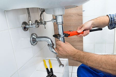 Plumbing Services Being Performed Under a Sink